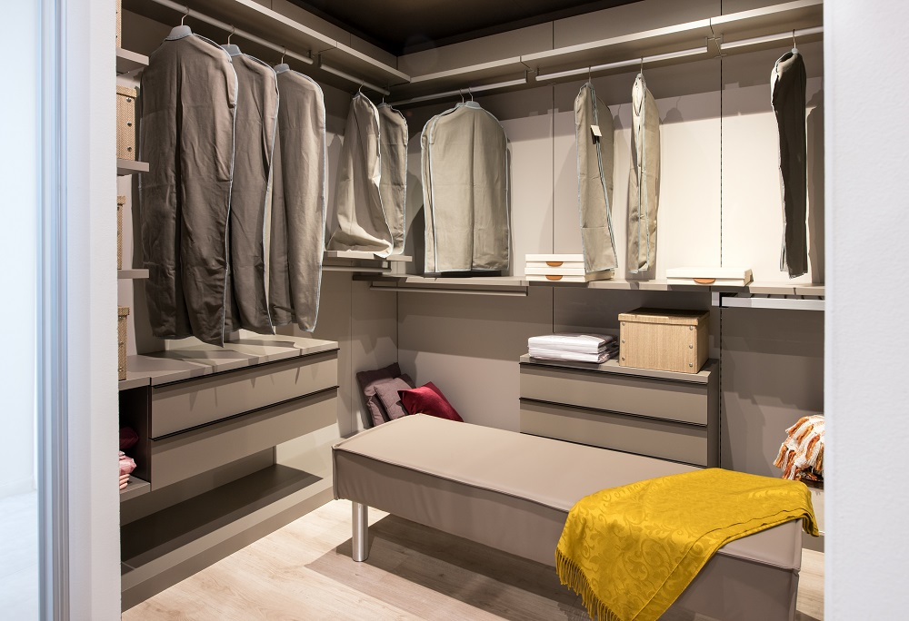 Interior of a walk in closet with hanging clothes and built in drawer units and seating in a luxury modern home